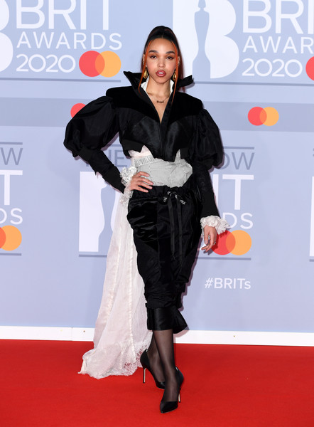 FKA Twigs looked flamboyant in a black-and-white Ed Marler ensemble, consisting of a cropped velvet pantsuit, gray boxer shorts, and a white shirt with a flowing train, at the 2020 BRIT Awards.