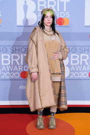 Billie Eilish teamed a chain-embellished Burberry trenchcoat with a matching top and pants for the 2020 BRIT Awards.