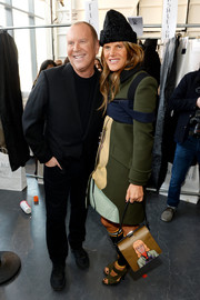 Anna dello Russo stood out, as always, in a face-print coat and a knit beanie during the Michael Kors fashion show.