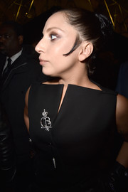 Lady Gaga adorned her little black dress with an eye-catching diamond and pearl pin when she attended the Balenciaga fashion show.
