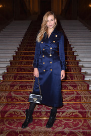 Natasha Poly looked perfectly stylish in a navy satin trenchcoat with gold buttons at the Balmain Fall 2018 show.