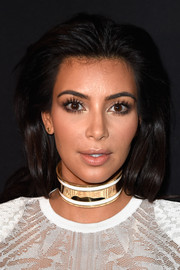 Kim Kardashian opted for a partless, brushed-back hairstyle when she attended the Balmain fashion show.
