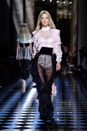 Alessandra Ambrosio got all frilled up in a pink lace and ruffle bodysuit for the Balmain runway.