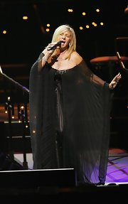 Barbra Streisand wore a dramatic sheer black off-the-shoulder gown for a performance at the O2 Arena.