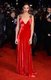 Gal Gadot wowed at the 'Batman v Superman' European premiere in a scarlet Prada gown with a plunging neckline and embellished shoulder straps.