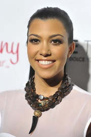 Kourtney Kardashian showed off a tribal inspired necklace with a interesting animal tooth.