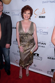 Caroline Manzo amped up the elegance with an embroidered gold cocktail dress at the Beach Bunny Swimwear fashion show.