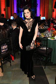 Dita Von Teese accessorized with an embellished frame clutch for some sparkle to her black gown at the 2017 Hulaween event.
