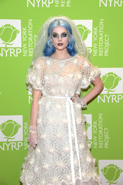 Lucy Boynton attended Bette Midler's Hulaween wearing sheer, fingerless gloves to match her white dress.