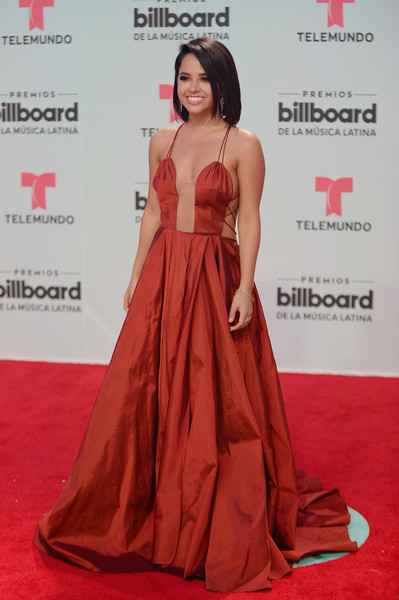 Becky G made a head-turning entrance at the Billboard Latin Music Awards in a brick-red Marmar Halim ball gown with an illusion front and lace-up sides.