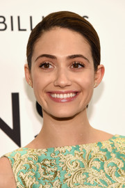 Emmy Rossum styled her hair in a pulled back bun to show off her polished makeup.