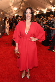 Dascha Polanco tied her look together with a gold box clutch.