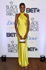 Leomie Anderson paired her dress with a metallic gold purse.