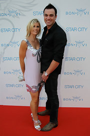 Shannon Noll complemented a silver sequin embellished dress with strappy metallic heels.