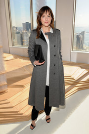 Dakota Johnson arrived for the Boss fashion show looking warm and stylish in a wool coat (in just one shade of gray).