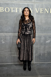 Salma Hayek paired a black lace dress with slouchy boots for a demure-meets-edgy vibe at the Bottega Veneta fashion show.