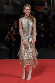 Emilia Jones finished off her monochromatic look with a gold box clutch.