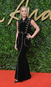 Rita Ora chose a military-inspired black velvet gown with gold trim and buttons for her British Fashion Awards red carpet look.