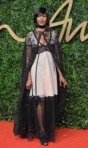 Naomi Campbell added more drama with a black lace cape, also by Burberry.