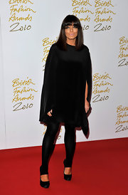 Claudia Winkleman donned a pair of black satin platform pumps with leggings tucked into them.