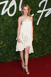 Kylie Minogue was boudoir-chic at the British Fashion Awards in an ivory Stella McCartney satin swing dress featuring an asymmetrical ruffle hem.