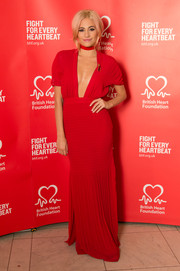 Pixie Lott dares to bare in this plunging V-neck red dress with a choker and pleated details.