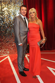 Christie Goddard accessorized with a textured gold metal purse at the British Soap Awards.