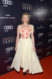 Haley Bennett channeled '50s glamour in an ivory Dior Couture fit-and-flare gown with red embellishments on the bodice for the 'Magnificent Seven' premiere in Toronto.