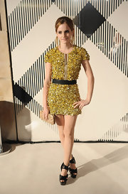 Emma Watson pulls her hair back into a loose bun to highlight her sparkling gold Burberry dress.