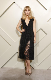 Suki Waterhouse paired shimmery gold pumps with her LBD for a totally classy look.