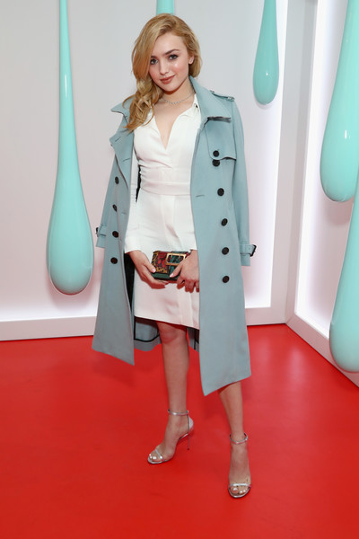 Peyton List arrived for the launch of Burberry's DK88 bag wearing a pastel-blue trenchcoat over a little white dress.