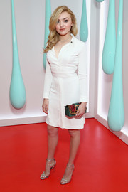 Peyton List punctuated her neutral look with a colorful snake/leopard-print clutch by Burberry.