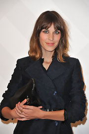 Alexa Chung gave her modern style an elegant finish with a black satin zippered clutch.