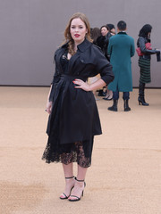 Tanya Burr attended the Burberry fashion show looking stylish in a navy trenchcoat layered over a lace dress.