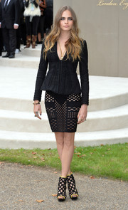 On the upper half, Cara Delevingne was a little more conservative in a textured, fitted black jacket, also by Burberry.