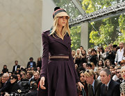 Cara Delevingne showed her waist by wearing a thick woven belt on top of her coat at the runway Burberry presentation.