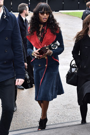 Naomi Campbell headed to the Burberry fashion show looking tres chic in navy and red suede coat from the brand.