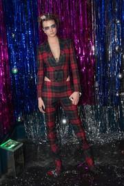 Cara Delevingne mixed a Christmas-y pantsuit with Halloween-inspired makeup for the Burberry x Cara Delevingne party.