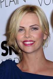 Charlize complements her colorful beauty look with a classic pair of gold hoops.