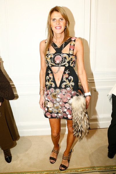 Black heels with metallic striped ankle straps completed Anna dello Russo's look.