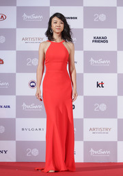 Tang Wei showed off her slim figure in a sleek, coral halter dress.