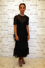 Alicia Vikander graced the Bulgari Tribute to Spanish Steps wearing a black sheer-overlay midi dress by Louis Vuitton.