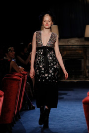 Ellie Bamber walked the Chanel Metiers D'art Collection Paris Cosmopolite runway wearing an elegantly embroidered V-neck dress.