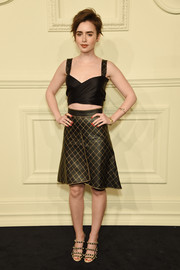 Lily Collins matched her crop-top with a black and gold grid-print skirt, also by Chanel.