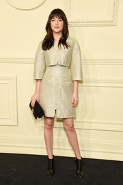 Dakota Johnson glimmered in a gold Chanel cropped jacket layered over a matching cinched-waist dress during the brand's Paris-Salzburg show.