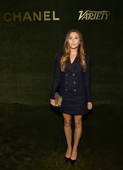 Elizabeth Olsen styled her dress with a metallic gold clutch.
