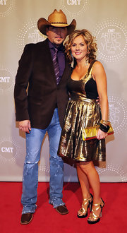 Jessica Aldean was golden in strappy gold and black platform heels. The metallic sandals matched a gilded dress and shiny clutch.
