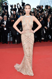 Bella Hadid commanded attention in a beaded nude Roberto Cavalli gown with a plunging neckline during the Cannes opening gala.