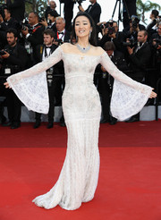 Gong Li looked regal at the Cannes opening gala in a white lace off-the-shoulder gown with bell sleeves.