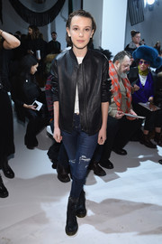 Millie Bobby Brown toughened up in a black leather jacket by Vince for the Calvin Klein fashion show.